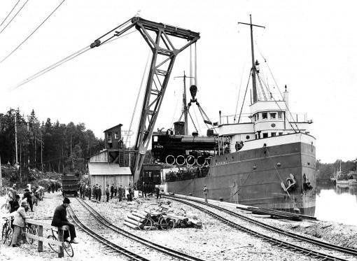 """S/S NEEBING lastar lok vid """"Rysskajen"""" i Trollhättan. Kranen är byggd på Götaverken och uppsattes våren 1922. Notera rälsen med två olika spårvidder."""