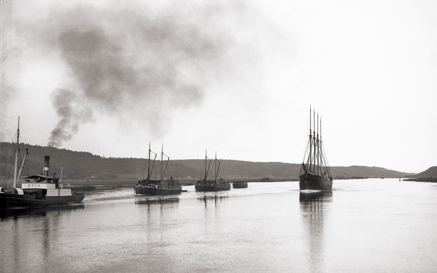 Längs Göta älv. 4-mastad skuta, sannolikt är det danskbyggda DROGDEN byggd 1917 som passerar ZEUS med tre pråmar på släp. Foto: glasplåt med okänd fotograf ca 1920. Ur Vänersborgs museums samlingar.