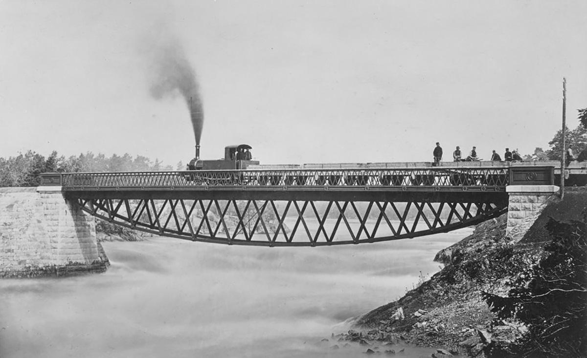 """Tågsätt på Stålbron, troligtvis provbelastning år 1866. Loket är UWHJ 1 """"Trollhättan"""". Foto: okänd"""
