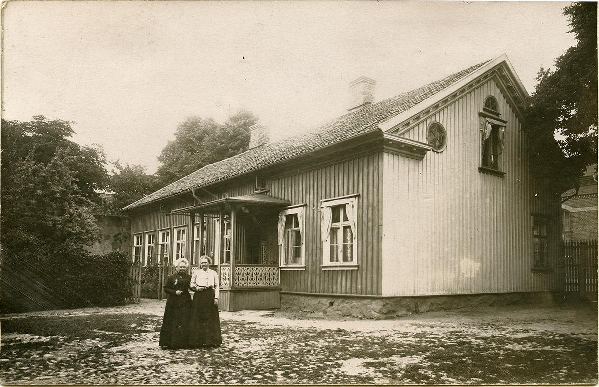 """""""Josse och Ingeborg Lundström statera framför ingångsverandan"""" Foto ur Emil Berggrens efterlämnade album. Gåva till Vänersborgs museum 1992."""
