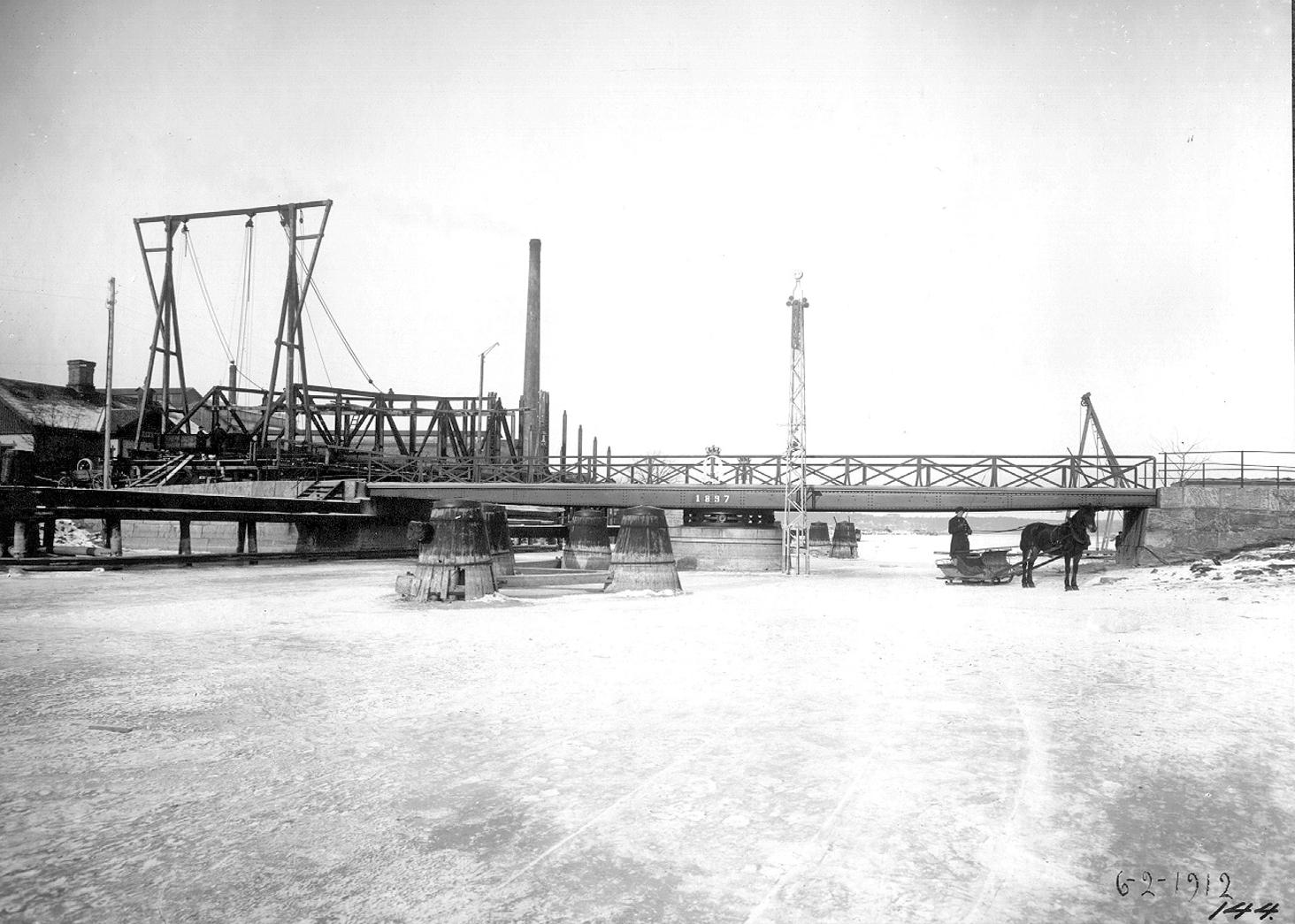 """1897 års svängbro över Karls grav. Den """"nya"""" bron ligger på land och väntar på att få komma på plats. Foto: Annie Wallén, 1912 (Innovatum)"""
